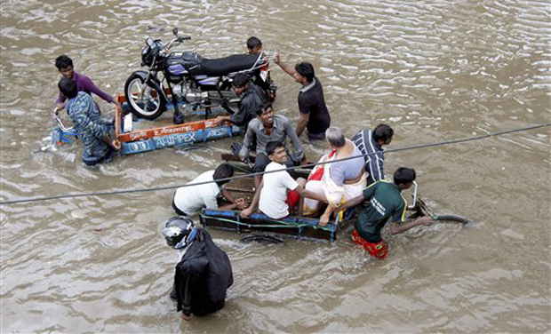 Chennai: People help a man carry his two-wheeler on a cycle cart as they wade through a waterlogged subway in Chennai on Monday. Heavy rains continue to lash several parts of the city as the Meteorological Department alerted a cyclone warning on the Bay of Bengal coast. PTI Photo (PTI11_9_2015_000242A)